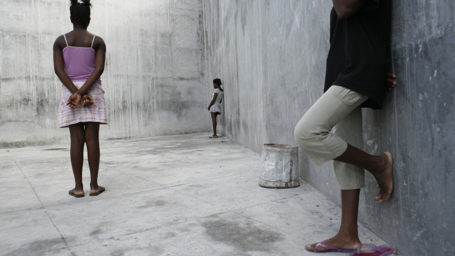 Three girls stand in the concrete yard of the women's prison at Pétionville, a suburb of Port-au-Prince, the capital. Behind her stands a concrete wall, topped with barbed wire. Laundry lies on the ground at her feet. Arrests of minors are frequently gang-related, with alleged offences ranging from petty crime to gun possession and assault. Children are often forcibly inducted into gangs, where they face violence from older gang members, rival gangs and the authorities. Many girls have been sexually abused, and some are HIV-positive. Once in prison, they can be held indefinitely without being charged or tried. UNICEF provides sanitation kits and educational and art supplies to this prison.  [#3 IN SEQUENCE OF SEVEN]  In December 2005 in Haiti, children face extreme poverty, violence and chronic insecurity. UNICEF's Child Alert Report on Haiti is the second in a series that documents the effect of crisis situations on children. The report, to be released on 22 March 2006, warns that decades-long political instability and weak institutions have created a climate of lawlessness and social disintegration that have exacerbated conditions of poverty. In addition, Haiti's vulnerability to natural disasters has deepened the environmental crisis of deforestation and erosion. The consequences for children are devastating. Each year, 20 per cent of children under five die from preventable illnesses, the highest child mortality rate in the Americas. Just 11 per cent of Haitians have running water in their homes, and 40 per cent have no access to safe water at all. Many thousands of children work as domestic servants or live in slums or on the streets, where they are vulnerable to gang violence, kidnapping and sexual exploitation. Only 54 per cent of children attend primary school, and of these, the majority leave school after just four years in order to work or care for younger siblings. More than 200,000 children have lost one or both parents to AIDS.